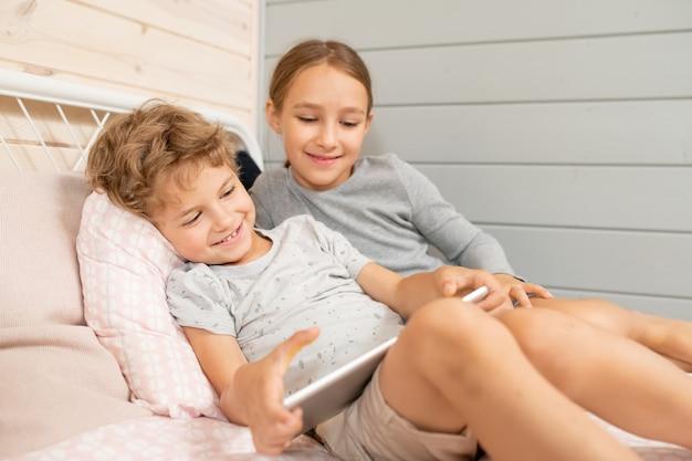 집에서 주말에 침대에서 휴식을 취하는 동안 터치패드로 온라인 만화를 보고 있는 홈웨어를 입은 행복한 귀여운 소년과 그의 행복한 여동생