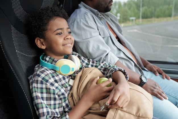 Счастливый милый маленький мальчик с яблоком и рюкзаком, сидя в автобусе
