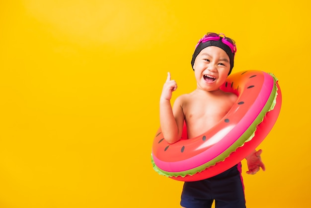 Happy cute little child boy wear goggles and swimsuit hold watermelon inflatable ring