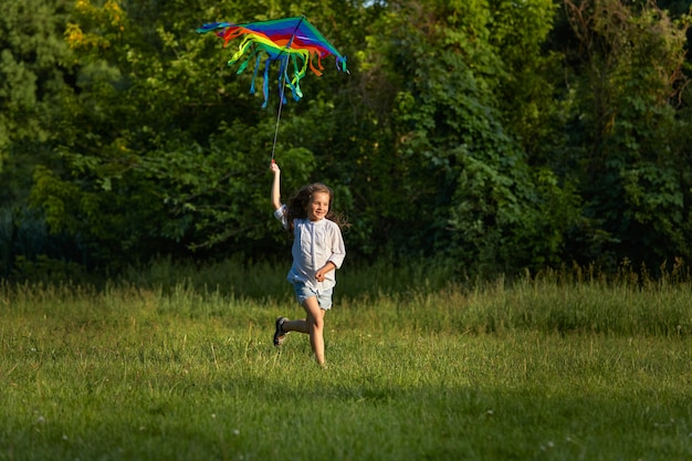 Happy cute little child girl launches kite in park in sunny summer day.