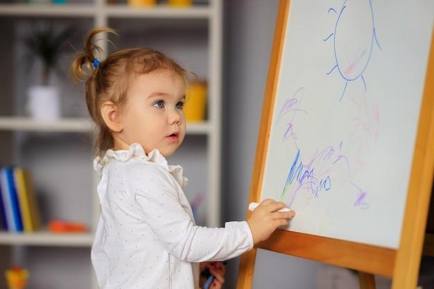 Счастливая милая маленькая девочка рисует на белой доске фломастером.