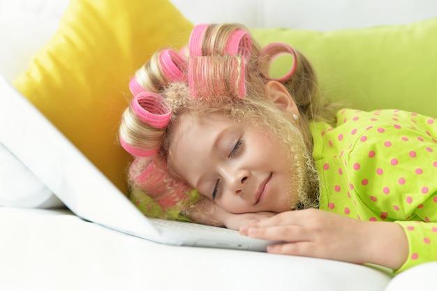 ラップトップで彼女のベッドで寝ているヘアカーラーで幸せなかわいい女の子