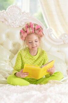 本とヘアカーラーで幸せなかわいい女の子