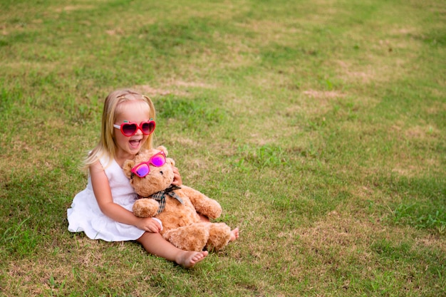 Happy cute little girl is wearing white dress sitting on the grass with her teddy bear toy in sunglasses
