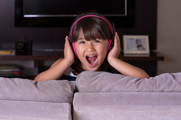 Счастливая милая маленькая девочка, слушающая музыку на диване у себя дома