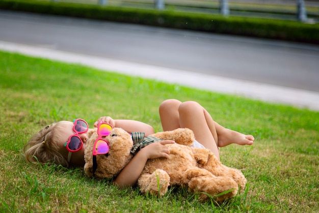 Happy cute little girl lying on the grass with her teddy bear toy in sunglasses