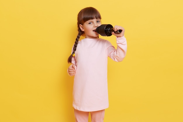 Happy cute little girl singing song on microphone while posing isolated over yellow background, dark haired female chile with pigtails sings in karaoke, looking at camera with excited and happy look.