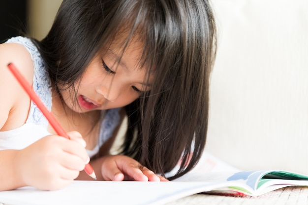 Happy cute little girl smiling and holding red pencil and drawing.