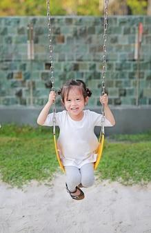 Happy cute little girl on swing in the park