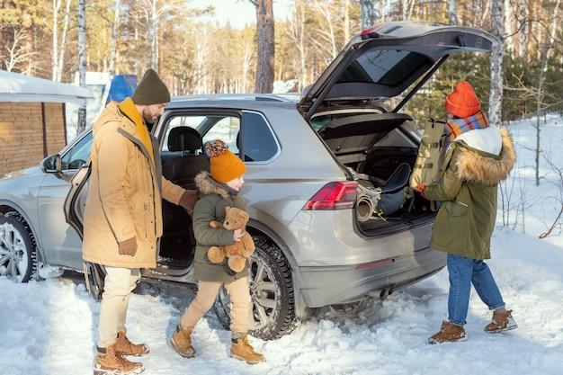 Счастливая милая маленькая девочка с медвежонком подходит к матери, вынимая рюкзак с багажом из багажника машины по прибытии в свой загородный дом