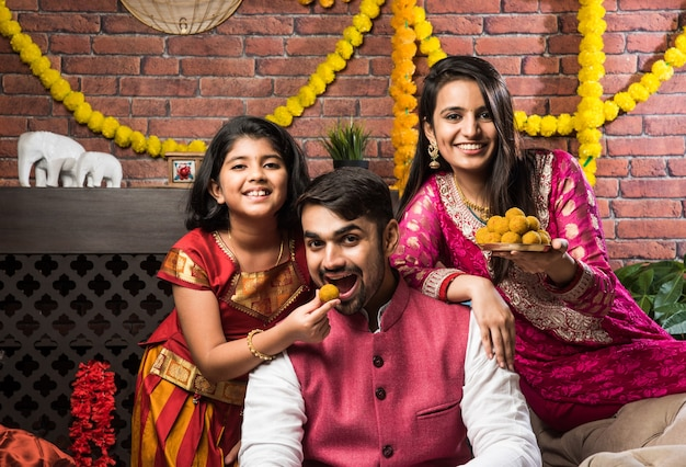 Happy cute little indian girl celebrating rakshabandhan or rakhi festival with big brother