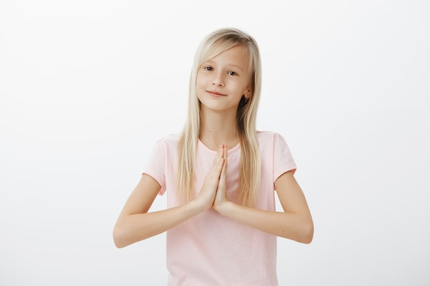 Happy cute little kid, blond woman saying thank you with hands clasped together, namaste gesture