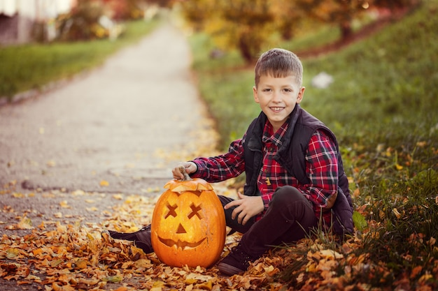 Happy cute little kid boy with halloween pumpkin in autumn park.