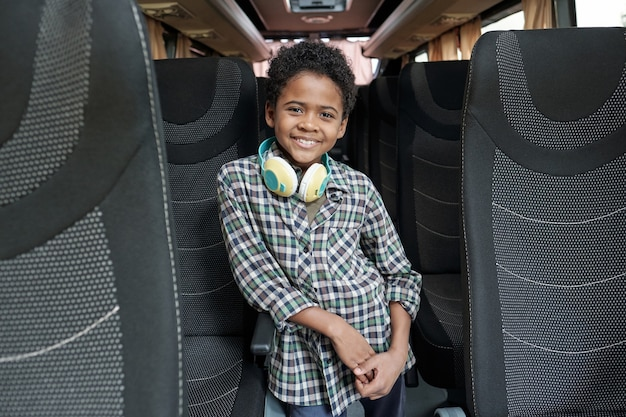 Счастливый милый маленький школьник в повседневной одежде, стоящий внутри автобуса