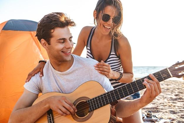 Счастливая милая влюбленная пара играет на гитаре на пляже на открытом воздухе