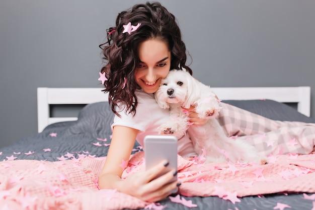 Momenti carini felici a casa con animali domestici di bella donna castana in pigiama. facendo selfie sul letto in orpelli rosa, sorridendo, esprimendo felicità