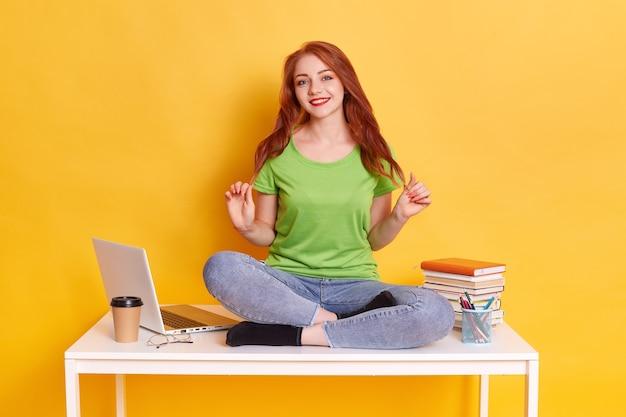 Счастливая милая красивая женщина, сидящая на столе со скрещенными ногами