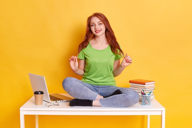 Happy cute pretty woman sitting on table with crossed legs