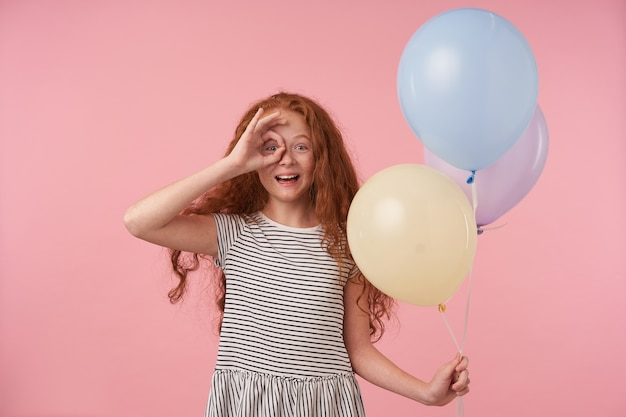 Happy cute redhead curly female kid raising hand with ok gesture to her eye, posing over pink background with air ballons, looking to camera joyfully and smiling widely