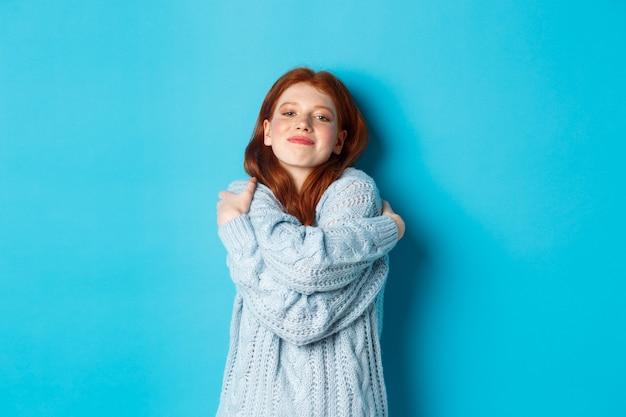 幸せなかわいい赤毛の女の子は、自分自身を抱き締め、快適で暖かいセーターを着て、カメラに微笑んで、青い背景の上に立っています。