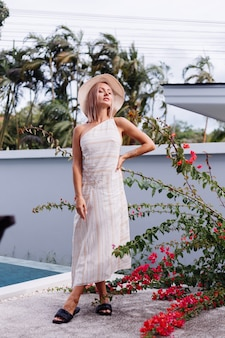 Felice carina romantica donna caucasica in estate elegante abito posteriore aperto bianco, cappello di paglia