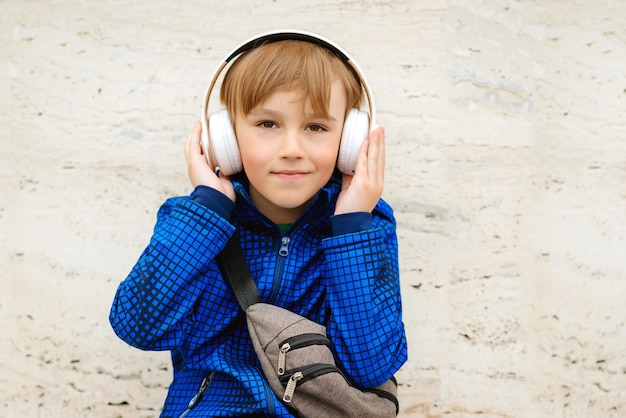 Happy cute schoolboy listening to music in headphones outside school.