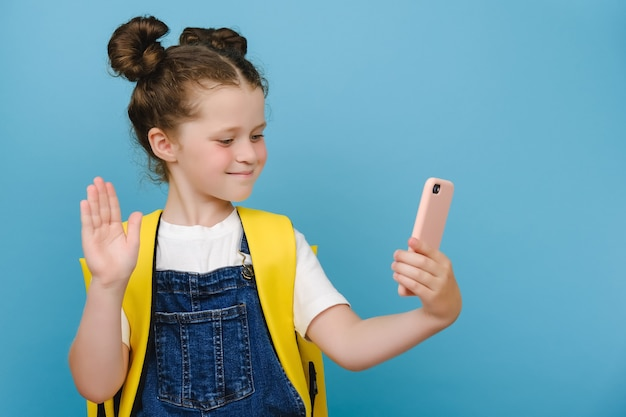 Happy cute schoolgirl with backpack holding phone, waving hand, video calling friend, family or school teacher during virtual meeting remote distance learning posing isolated on blue studio background
