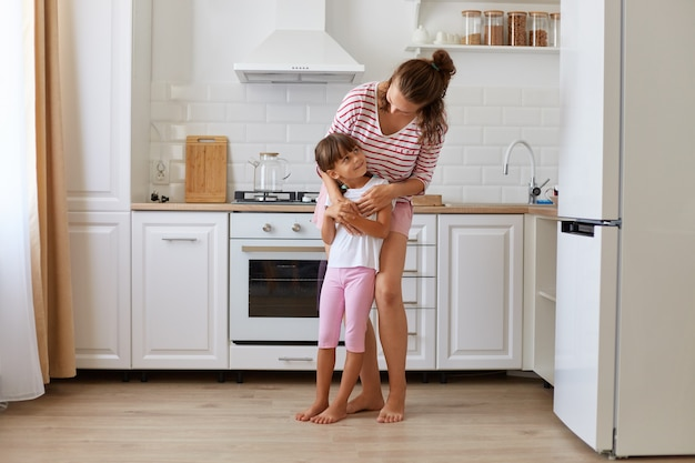 Happy cute small kid child daughter standing with mom having fun at home, standing in light kitchen room and hugging each other, motherhood and childhood.