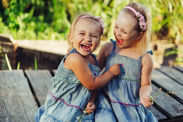 Happy cute smile children having fun play outdoors hug together. childhood,  nature, vacation, kids lifestyle concept | Premium Photo