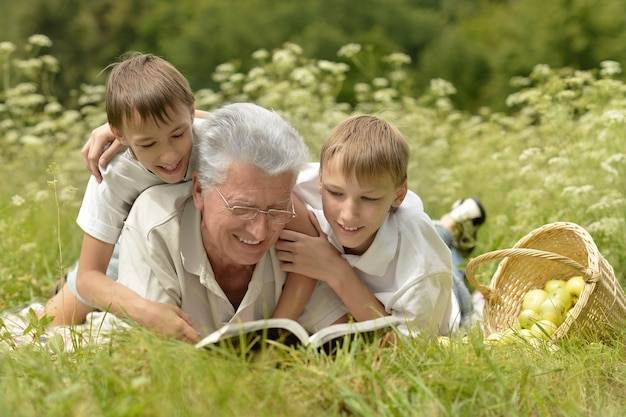 Happy cute smiling family with book on green summer grass with apples