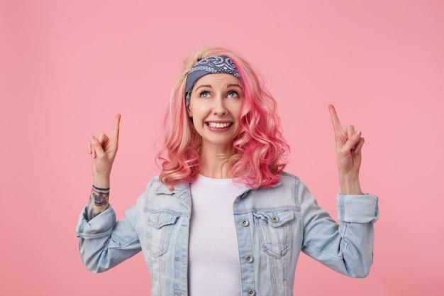 분홍색 머리와 문신 된 손, 서, 흰색 티셔츠와 데님 재킷을 입고 행복 귀여운 웃는 아가씨. 그녀의 머리 위의 복사 공간을 올려다보고 손가락을 가리 킵니다.