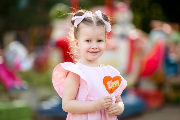 Счастливая милая сладкая девочка 4-5 лет на прогулках в парке ест вкусные конфеты