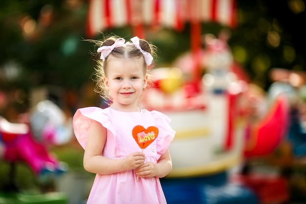 Happy cute sweet girl 4-5 years old amid rides in the park eating tasty candy