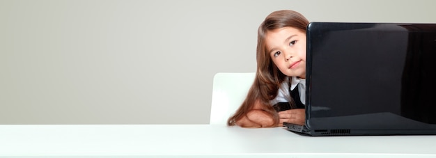 Happy and cute teen school girl sitting on laptop