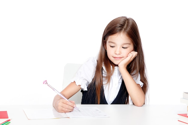 Happy and cute teen school girl writes in a book or notebook