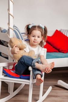 행복한 세 살배기 소녀가 아이들 방에 앉아 테디베어를 껴안고 있습니다. 테디베어가 집에서 의자에 앉아 카메라를 바라보고 있는 사랑스러운 운 좋은 작은 아이. 분위기 있는 아기의 가족 순간