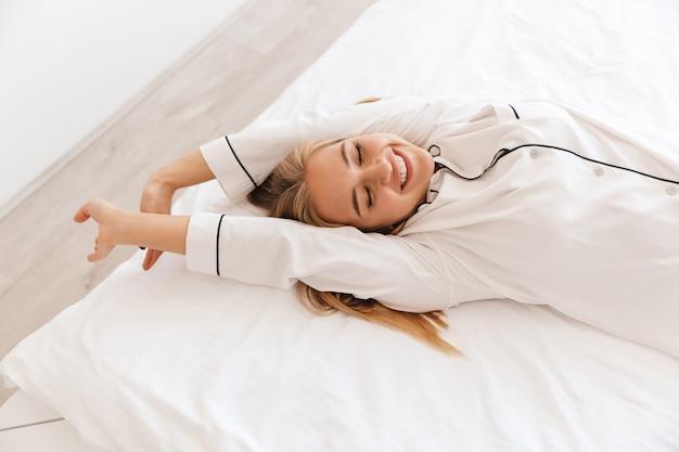 Счастливая милая женщина в пижаме протягивает руки и улыбается, лежа на кровати после сна