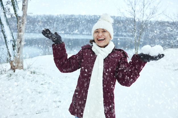 片手に雪玉を持って、雪が降るのを楽しんで白いウールの帽子とスカーフで幸せなかわいい女性