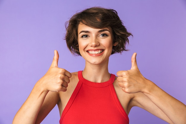 Happy cute woman isolated over purple wall background showing thumbs up gesture.