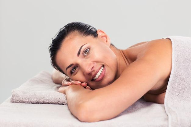 Счастливая милая женщина, лежа на массажном шезлонге