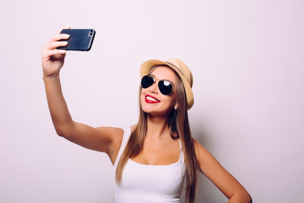 Donna sveglia felice che fa selfie isolato sopra il muro grigio.
