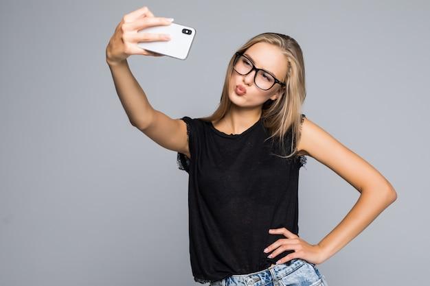 Счастливая милая женщина, делающая селфи на телефоне на сером фоне.