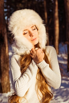彼女の目を閉じて冬の森で白い毛皮の帽子をかぶって幸せなかわいい女性