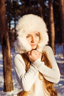 Happy cute woman wearing white fur hat in winter forest