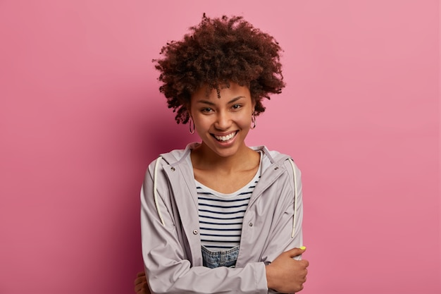 Happy cute woman with timid calm face expression, crosses hands over body