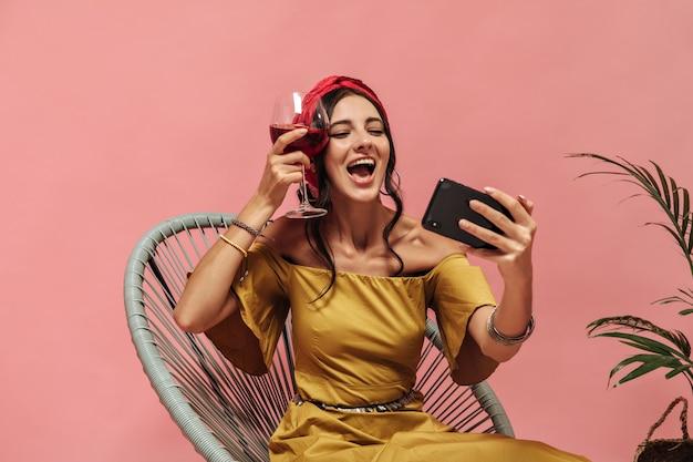 Felice donna carina con capelli scuri ondulati in bandana rossa e orecchini in posa con smartphone e con in mano un bicchiere di vino sul muro rosa
