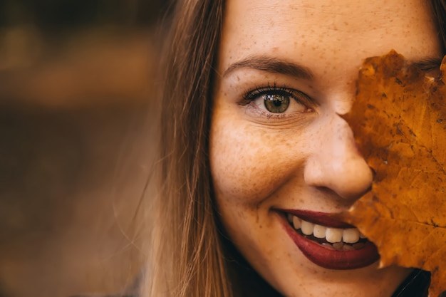 笑顔で幸せなかわいい若い魅力的な女性が公園に立って、彼女の顔を覆います