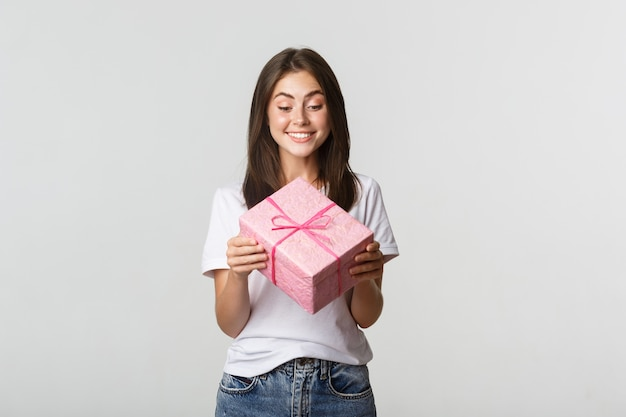 幸せなかわいい若い誕生日の女の子、笑顔でb-dayギフトを見てください。