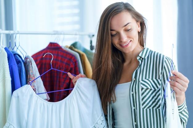 布の店で衣料品の買い物中にトレンディなスタイリッシュなトレンディな女性の服を選択する幸せなかわいい若いブルネットの女性