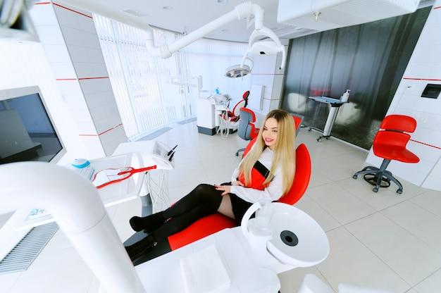 Счастливая милая маленькая девочка усмехаясь пока сидящ в зубоврачебном стуле
